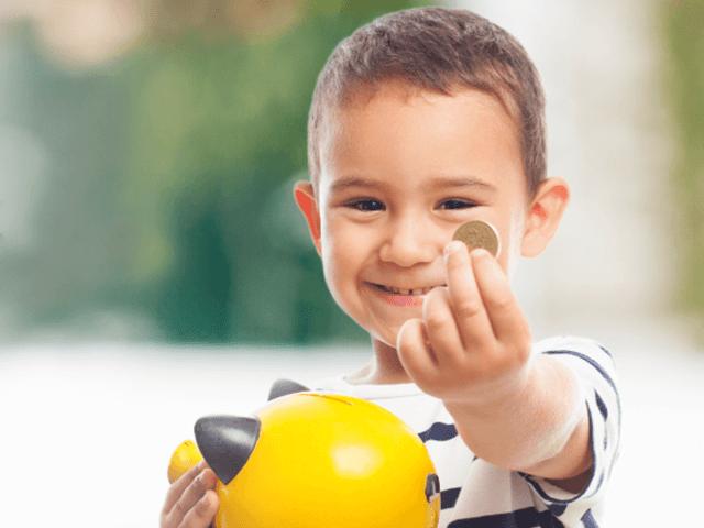Niño sosteniendo una alcancía y mostrando una moneda